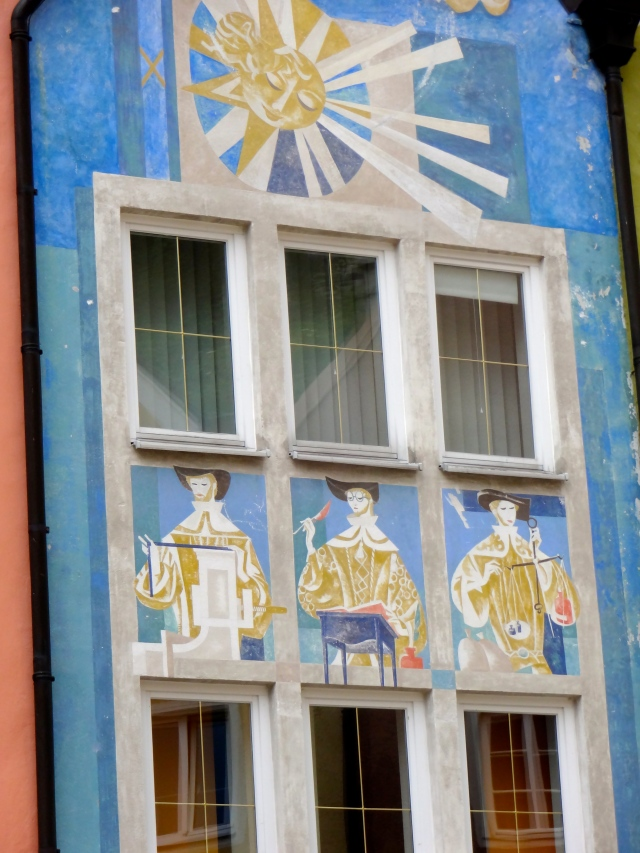 Many of the buildings have paintings on them.